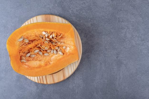 Une demi-citrouille sur une assiette en bois, sur la surface en marbre.