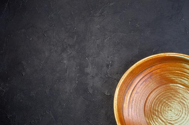 Demi-coup d'une assiette ronde de couleur bleu doux et marron sur fond noir avec espace libre