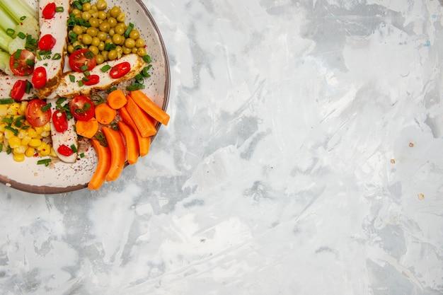Demi-coup de délicieuse salade végétalienne sur une assiette sur une surface blanche avec espace libre