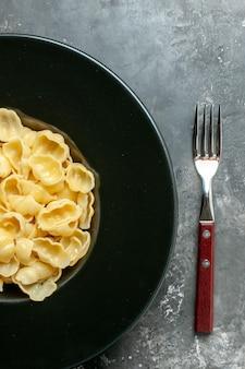 Demi-coup de délicieux conchiglie sur une assiette noire et un couteau sur fond gris