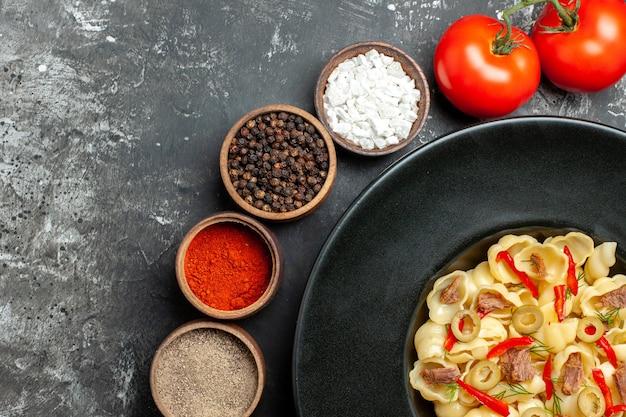 Demi-coup de délicieux conchiglie avec des légumes verts sur une assiette et un couteau et différentes épices tombées d'une bouteille d'huile sur une table grise