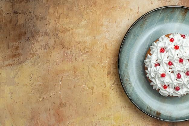 Demi-coup de délicieux gâteau décoré de crème et de groseille sur une plaque bleue sur le côté gauche sur fond coloré