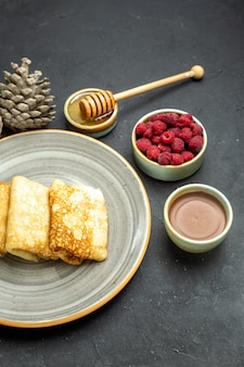 Demi-coup de fond de dîner avec de délicieuses crêpes au miel et au chocolat framboise et cône de conifère sur fond noir