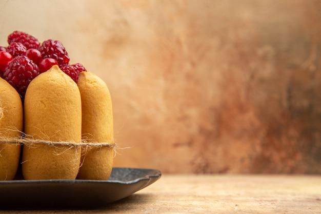 Demi-coup d'un gâteau-cadeau avec des fruits sur le côté droit de la table de couleurs mixtes
