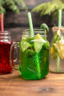 Demi-coup de jus de fruits frais biologiques dans des bouteilles servis avec des tubes et des fruits sur un fond en bois marron