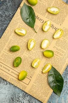 Demi-coup de kumquats frais coupés en deux et de feuilles sur des journaux sur fond gris