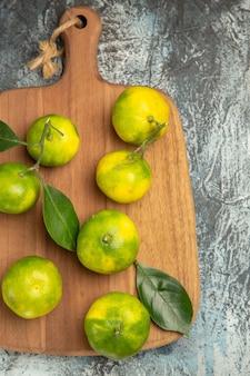 Demi-coup de mandarines vertes fraîches avec des feuilles sur une planche à découper en bois sur fond gris photo stock