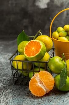 Demi-coup d'un panier et d'un seau plein de mandarines vertes fraîches coupées en deux et de mandarines pelées sur fond gris