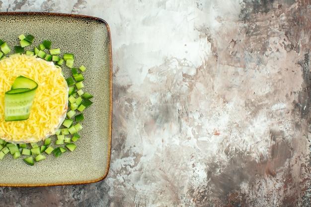 Demi-coup de salade savoureuse servie avec du concombre haché sur le côté droit sur une table de couleurs mélangées
