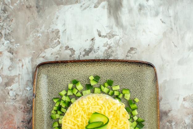 Demi-coup de salade savoureuse servie avec du concombre haché sur fond de couleur mélangée