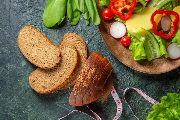 Demi-coup de tranches de pain noir de légumes frais hachés sur une assiette et des mètres de paquet vert sur la surface de couleurs foncées