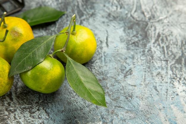 Demi-coup et vue horizontale de mandarines vertes fraîches avec des feuilles vertes sur fond gris