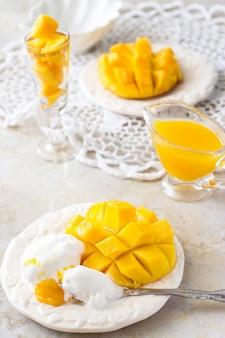 Demi cubes de crème glacée et de fruits de mangue et purée de jus de mangue sur fond blanc en béton.
