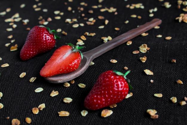 Demi fraise sur une cuillère en bois, près des baies entières et flocons sur un fond noir.