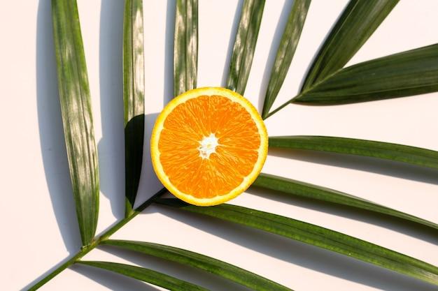 Demi fruit orange sur des feuilles de palmier tropical