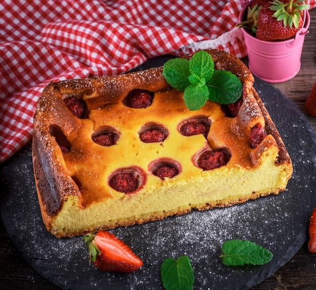 Un demi-gâteau au fromage aux fraises sur une assiette en graphite noir