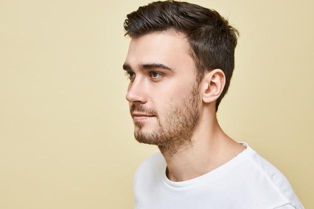 Demi-image de profil de beau jeune homme de race blanche avec une bonne peau, yeux bruns, cheveux noirs élégants et chaume posant isolé contre un mur blanc, regardant en face de lui, souriant