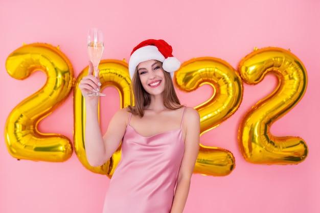 La demi-longueur d'une fille souriante lève une coupe de champagne dans des ballons à air de chapeau de père noël nouvel an