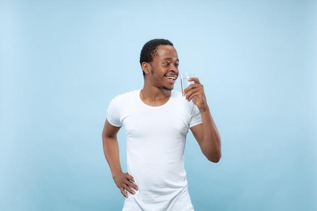 Demi-longueur gros plan portrait de jeune homme afro-américain en chemise blanche sur l'espace bleu