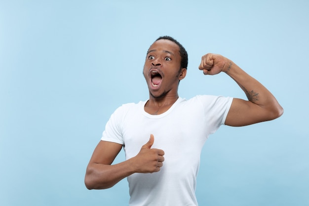 Demi-longueur gros plan portrait de jeune homme afro-américain en chemise blanche sur fond bleu. émotions humaines, expression faciale, publicité, concept. célébrer, émerveillé, étonné, choqué, fou heureux.