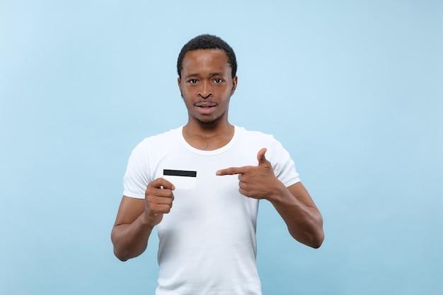 Demi-longueur gros plan portrait de jeune homme afro-américain en chemise blanche sur fond bleu. émotions humaines, expression faciale, publicité, concept de vente. pointant sur la carte. paiements, finances, facture.