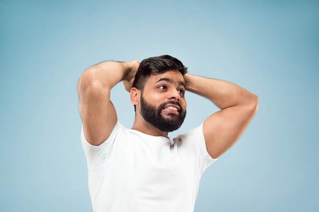 Demi-longueur gros plan portrait de jeune homme en chemise blanche sur bleu
