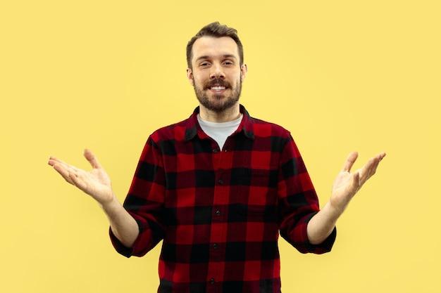 Demi-longueur gros plan portrait de jeune homme en chemise sur l'espace jaune. les émotions humaines, le concept d'expression faciale. vue de face. couleurs à la mode. espace négatif