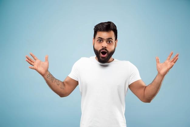 Demi-longueur gros plan portrait de jeune homme hindou en chemise blanche sur l'espace bleu