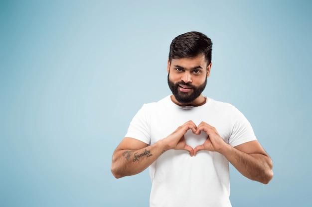 Demi-longueur gros plan portrait de jeune homme hindou en chemise blanche sur fond bleu. émotions humaines, expression faciale, concept publicitaire. espace négatif. montrant le signe du cœur. souriant.