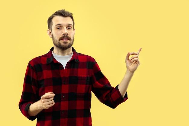 Demi-longueur gros plan portrait de jeune homme sur mur jaune.