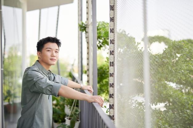 Demi-longueur de jeune bel homme debout sur un balcon extérieur,
