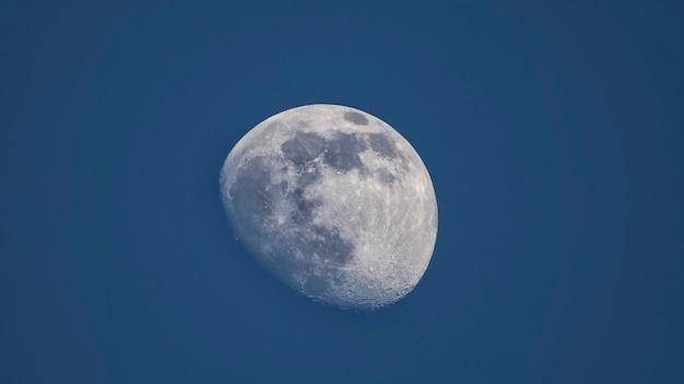 Demi lune illuminée sur fond de ciel bleu