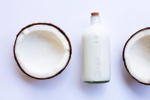 Demi noix de coco avec une bouteille de lait de coco sur blanc