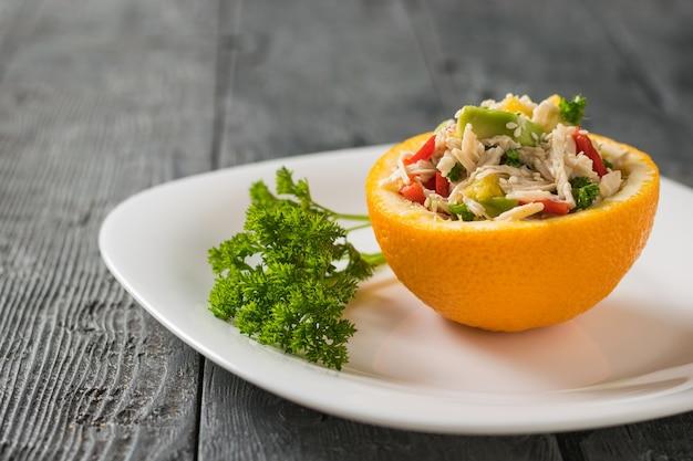 Une demi-orange remplie de salade sur une assiette blanche avec un brin de persil