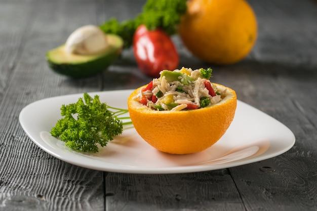 Une demi-orange avec une salade d'avocat et du poulet avec du persil sur une assiette blanche. aliments diététiques de fruits tropicaux et de poulet.