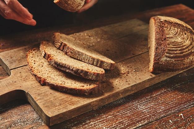 Demi et pain tranché sur une vieille planche en bois