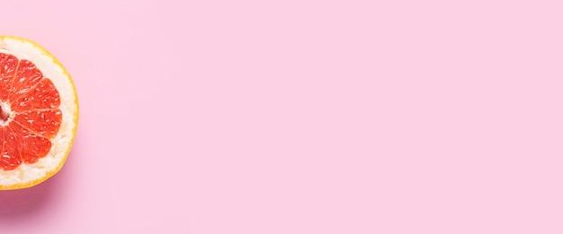 Demi pamplemousse sur fond rose. fermer. bannière. mise à plat, vue de dessus