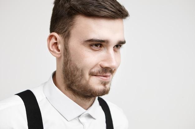 Demi-photo de profil de jeune homme à la mode à la recherche amicale avec moustache et barbe souriant pensivement alors qu'il rappelle une histoire drôle ou une blague, posant en studio portant une chemise formelle blanche