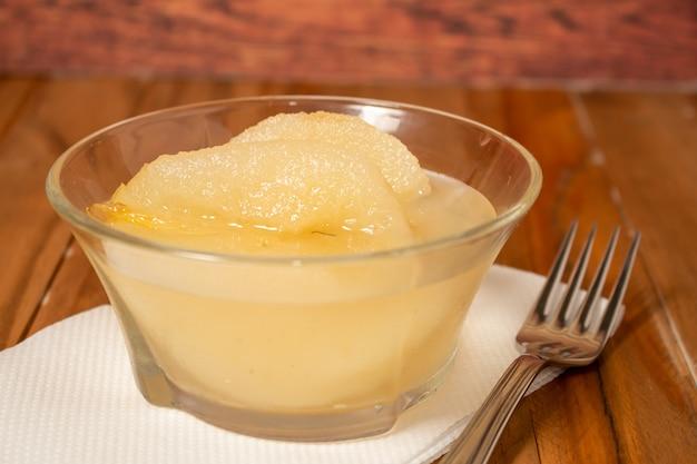 Demi-poires fraîches servies avec sirop sucré. fond de table en bois.