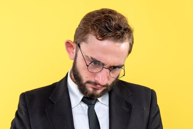 Demi portrait de jeune commerçant se concentrant sur quelque chose sur le jaune