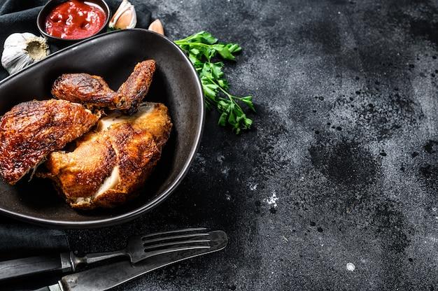 Un demi-poulet grillé sur une assiette. fond noir. vue de dessus. espace copie