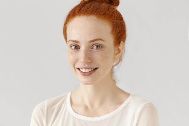 Demi-profil de belle rousse avec une peau saine de taches de rousseur et un chignon souriant