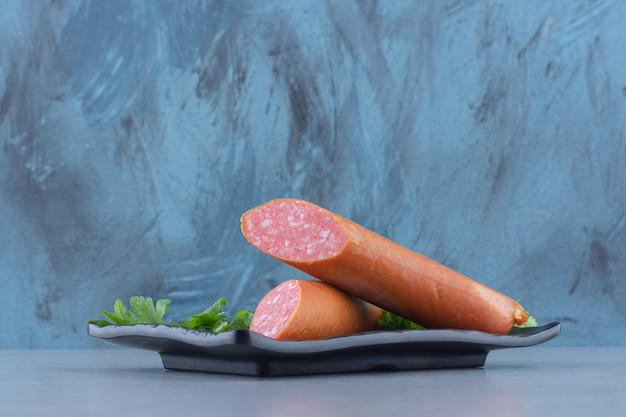 Demi-salami coupé sur plaque noire.