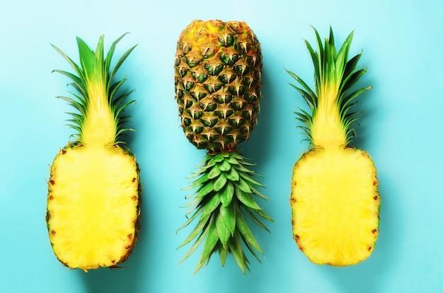 Demi tranche d'ananas frais et fruit entier sur bleu