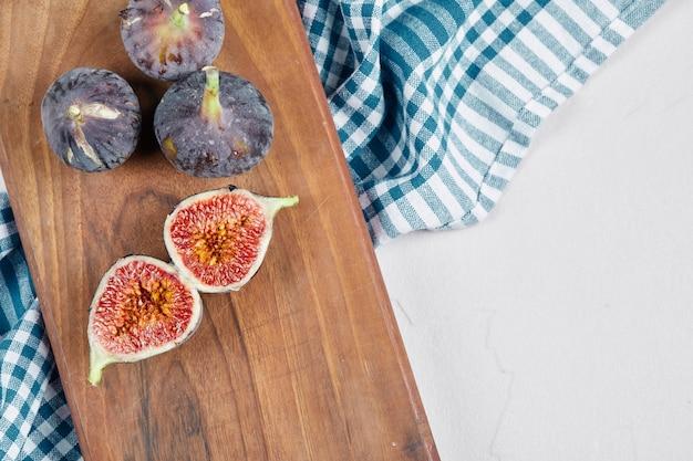 Demi-tranches et figues entières sur planche de bois avec une nappe bleue.