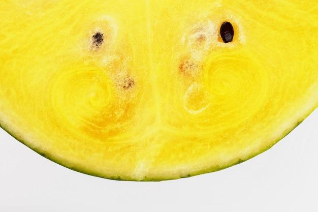Demi-tranches de melon d'eau jaune savoureux et mûr sur une texture blanche et isolée de pulpe juteuse