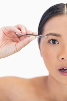 Demi visage d'une femme naturelle surprise à l'aide d'une pince à épiler