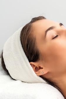 Demi visage de jeune femme aux yeux fermés en attente de procédure cosmétique