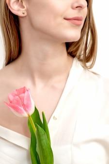 Demi-visage portrait d'une belle jeune femme de race blanche avec une tulipe rose sur fond blanc