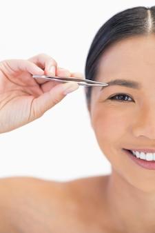 Demi visage de souriante femme naturelle à l'aide de pinces à épiler